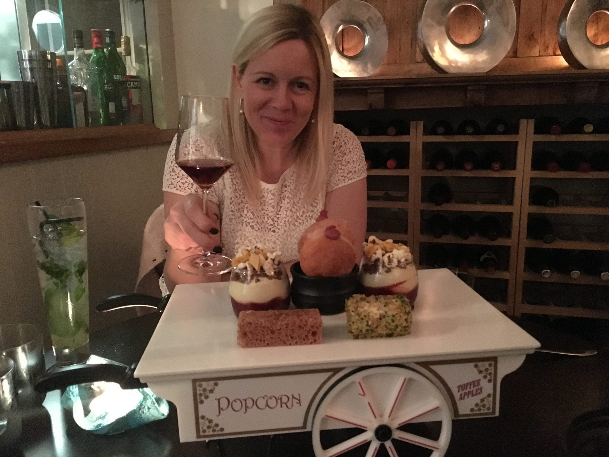 Image of a blonde, smiling woman holding a glass of wine, with a tray of food on the table in front of her.