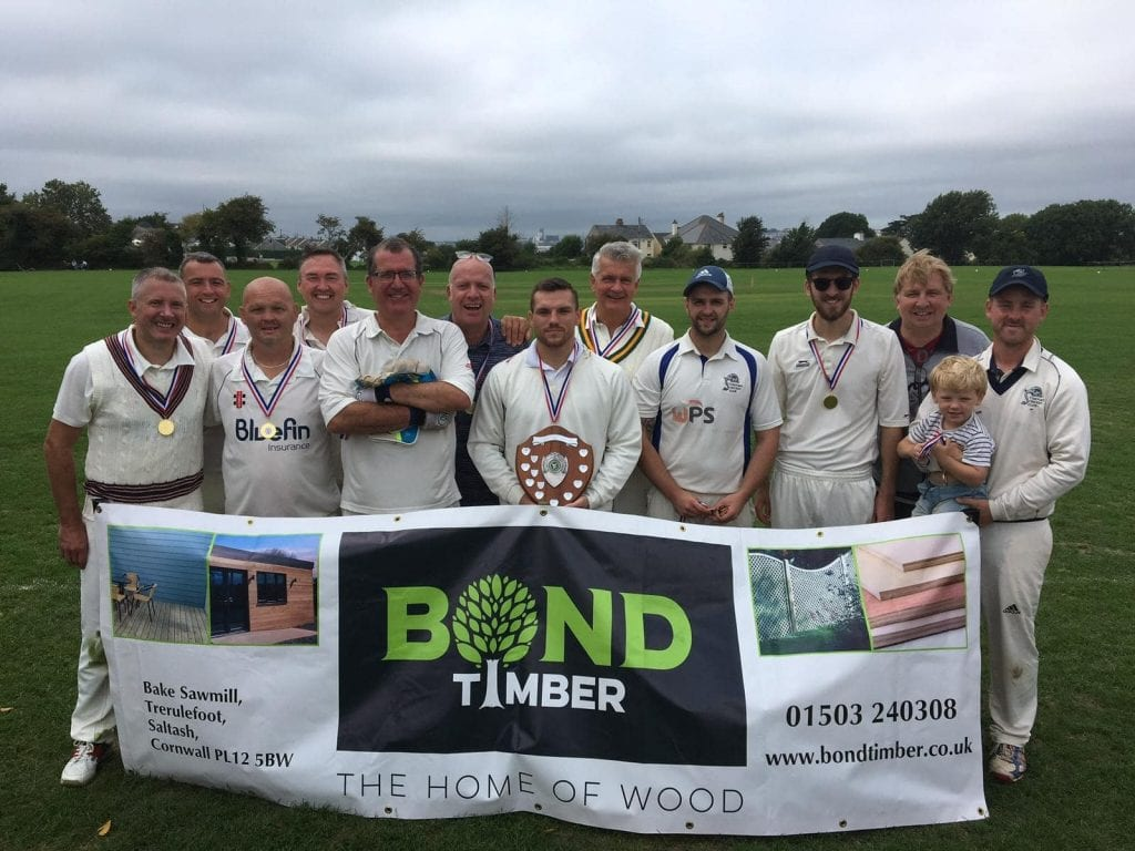 Image of a team of male cricketers, wearing their whites and posing on a field, whilst stood behind a banner.